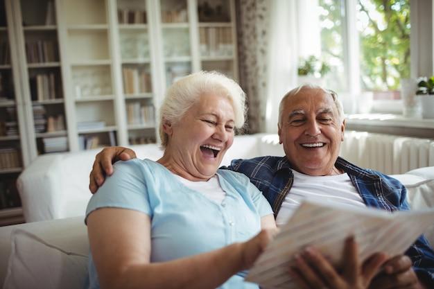 Пожилая пара смотрит на фотоальбом