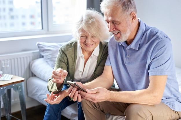 スマートフォン、オンラインsurfung net、現代の技術コンセプトで子供の写真を見ている年配のカップル。携帯電話を使用している白人の女性と男性は、福祉の家で一緒にソーシャルメディアを共有しています。
