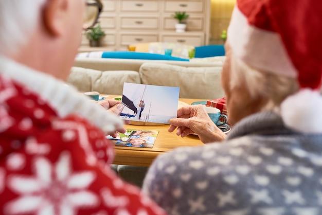 クリスマスに家族の写真を見て年配のカップル