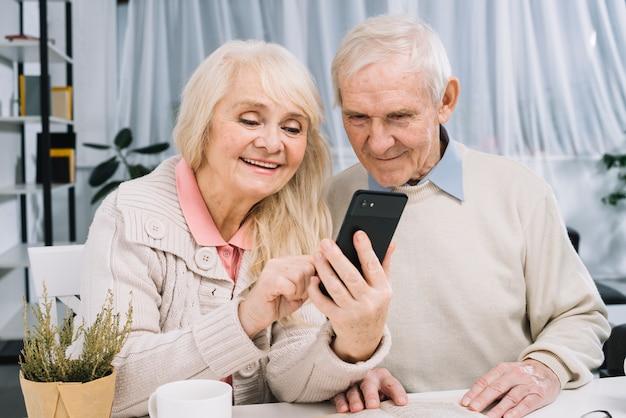 Пожилая пара смотрит на смартфон
