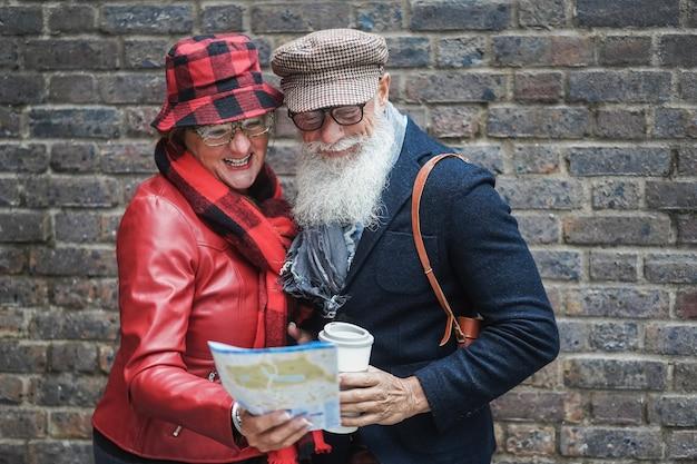 一緒に街を探索しながら旅行地図を見ている年配のカップル-年配の男性の顔に焦点を当てる
