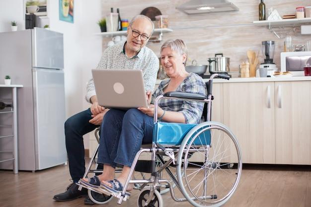 ビデオ通話の前にウェブカメラを見ている年配のカップル。車椅子の障害者の年配の女性と彼女の夫がキッチンのタブレットpcでビデオ会議を行っています。麻痺した老婆と彼女の夫は