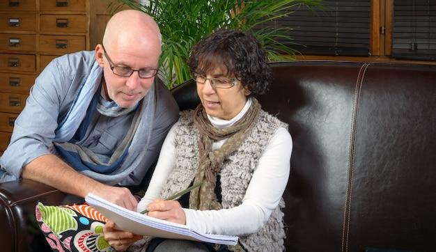 Senior couple looking a book on a sofa
