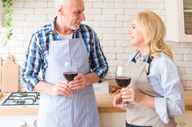 Senior couple looking at each other holding wine glasses in hand standing in the kitchen