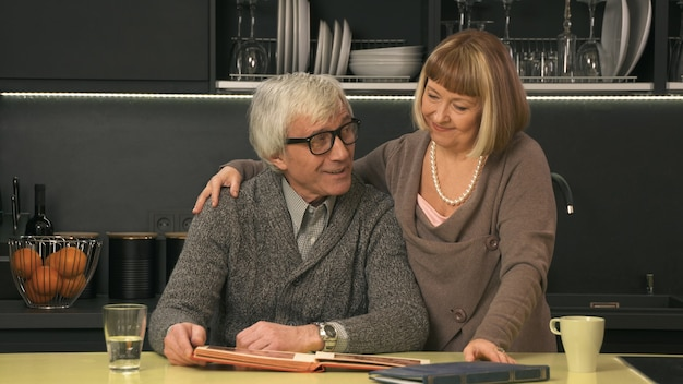 Senior couple looking old photo album and smiling
