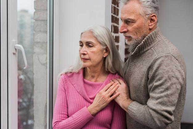 Пожилая пара смотрит в окно
