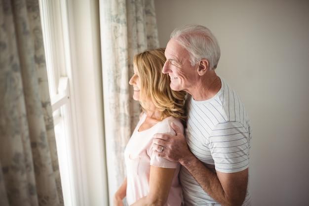 Старшая пара, глядя из окна