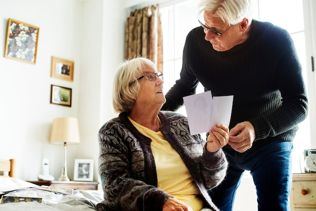 Senior couple looking at photos in the room together
