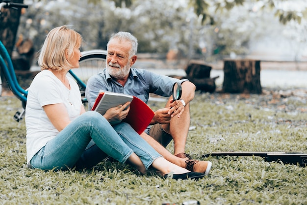 Senior couple in love sitting reading book with magnifying glass on grass in the park