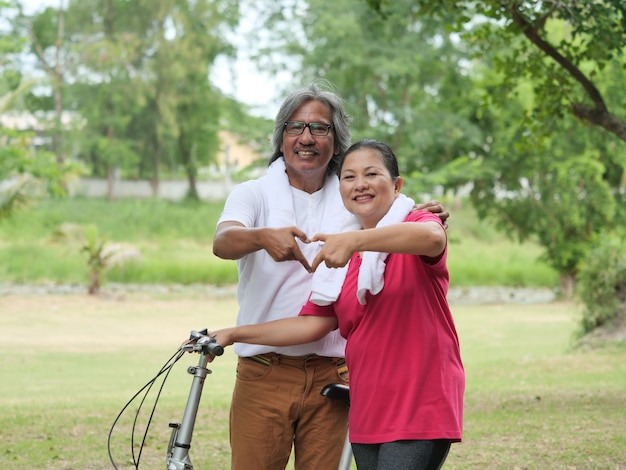 Senior couple lover cycling in park
