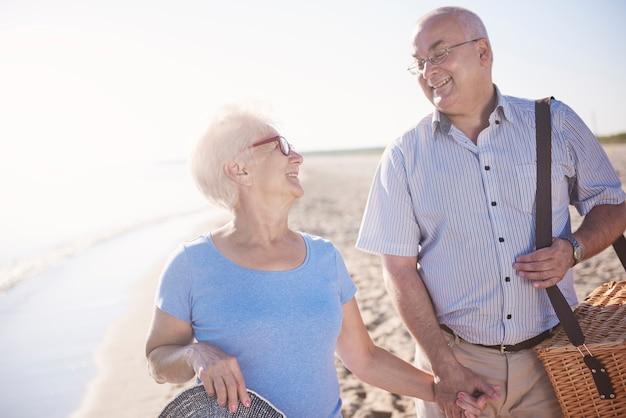 Senior couple loving picnics on the beach