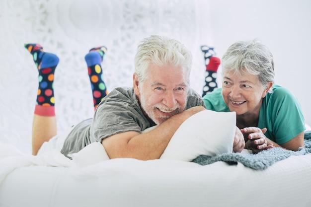 横臥とベッドに笑みを浮かべて年配のカップル。現代の家で快適なベッドに横たわってお互いに余暇を過ごす老夫婦。家で休んでいる陽気なカップル