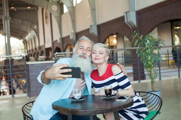 年配のカップルは、カフェで携帯電話を使用してselfieを作ります。
