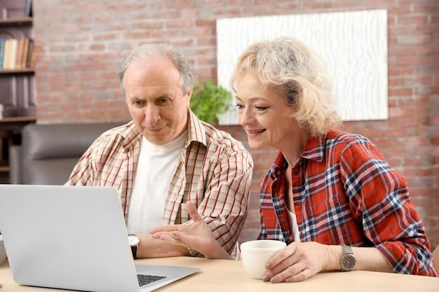自宅でノートパソコンを使ってビデオ通話をするシニア夫婦