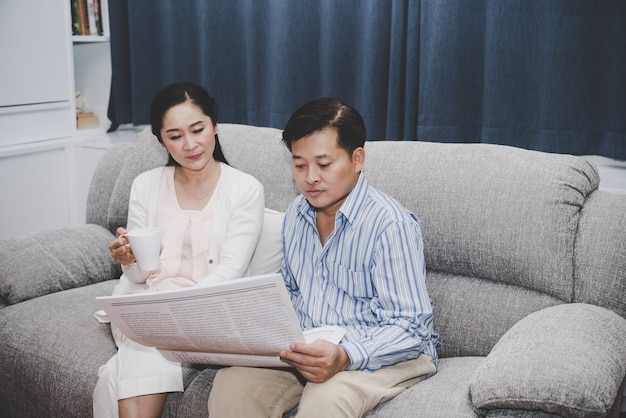 Senior couple a man reading newspaper with a woman holding cup of coffee sitting together on sofa in living room
