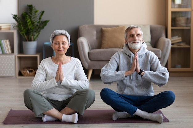 Senior couple meditating at home
