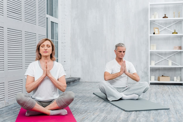 Senior couple meditating with praying hands on yoga mat at home