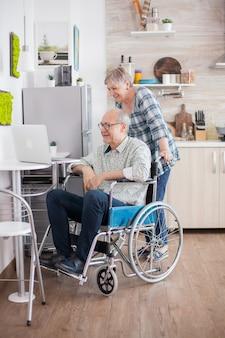キッチンでビデオ通話をしている年配のカップル。車椅子の障害者の年配の男性と彼の妻が台所のラップトップでビデオ会議を行っています。オンライン会議をしている麻痺した老人と彼の妻。