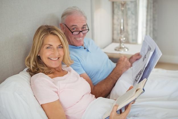 新聞や本を読んでベッドの上の年配のカップル