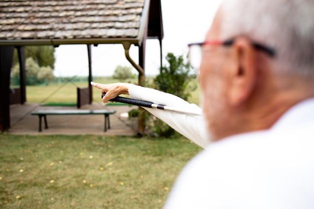 Старшая пара на поле для гольфа любит смотреть игровой турнир.
