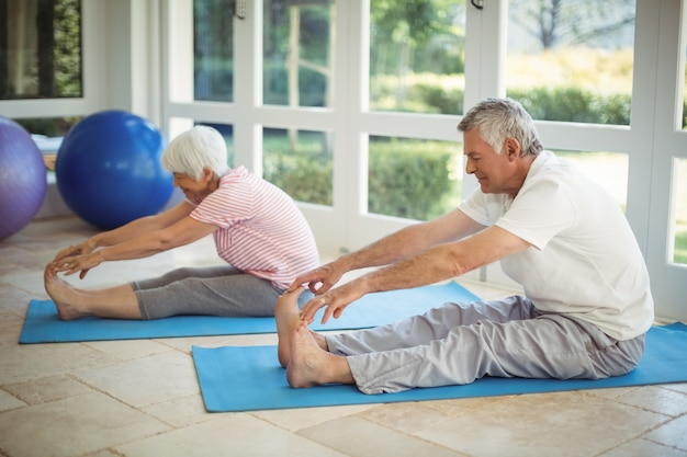Senior couple performing stretching exercise on exercise mat