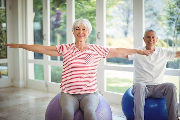 Senior couple performing stretching exercise on fitness ball