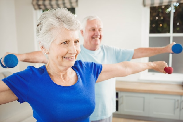 Senior couple performing stretching exercise with dumbbells at home