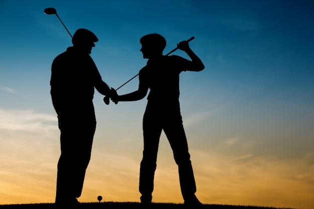 Senior couple playing golf at sunset