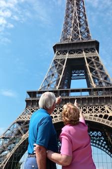 Coppia senior indicando torre eiffel a parigi