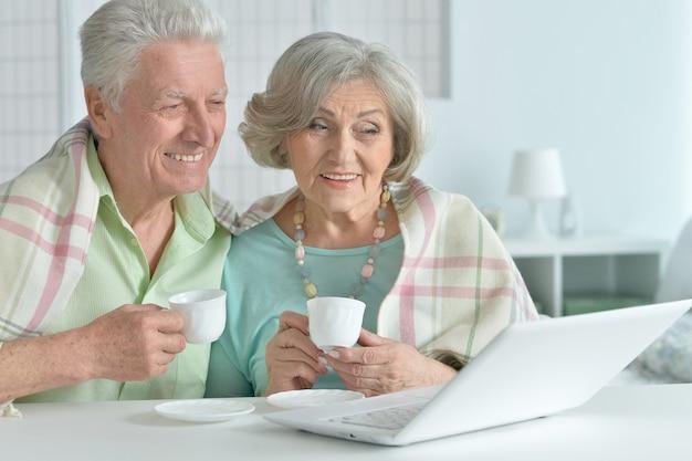 Портрет старшей пары с ноутбуком и чаем дома
