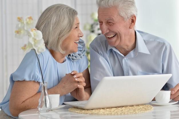 Портрет старшей пары с ноутбуком дома