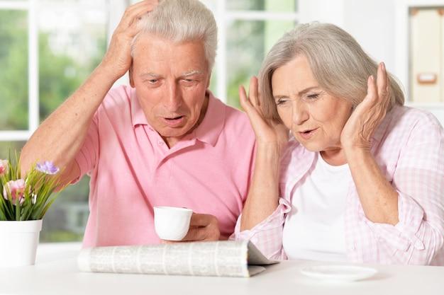 自宅で新聞と年配のカップルの肖像画