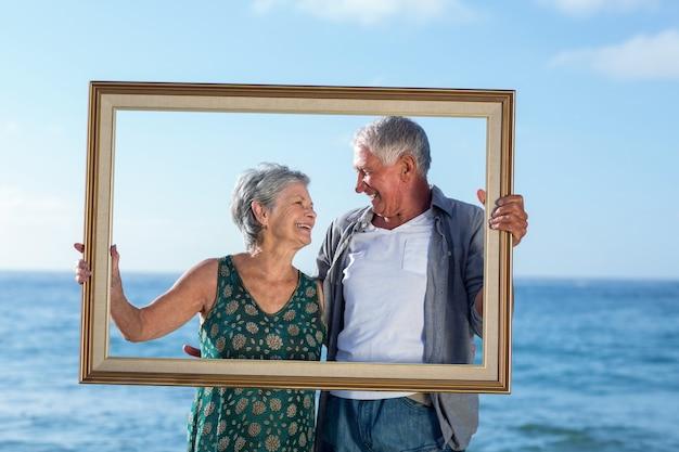 Старшая пара позирует с рамкой