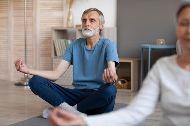 Старшая пара, практикующая йогу дома