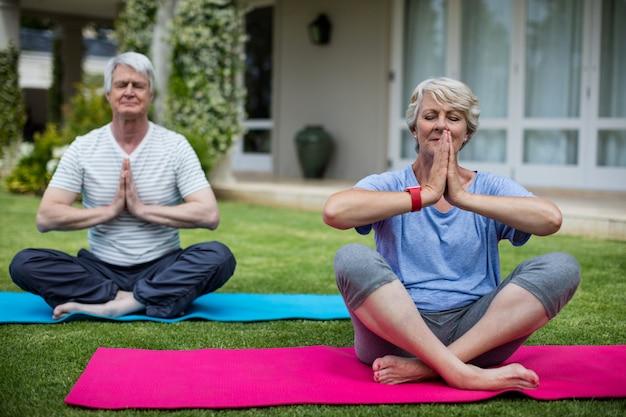Пожилая пара практикующих йогу на тренировочный мат