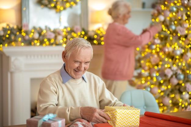 クリスマスプレゼントを準備し、クリスマスツリーを飾る年配のカップル