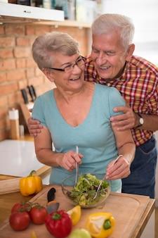 一緒に新鮮なサラダを準備する年配のカップル