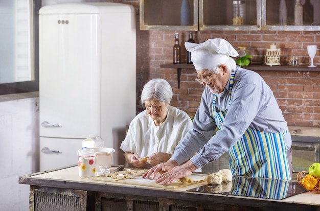 Senior couple preparing pastries in kitchen at home. man is wearing chef hat.