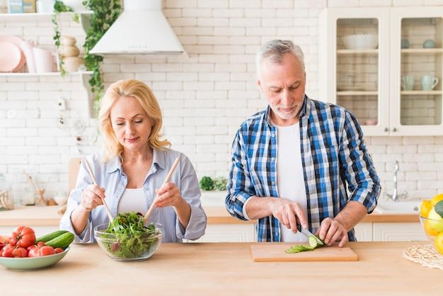 年配のカップルがモダンなキッチンでサラダを準備します。