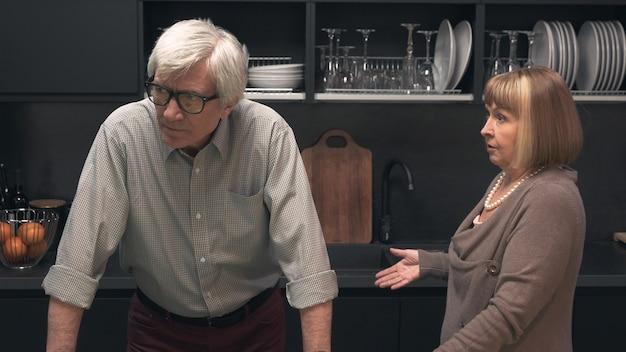 キッチンのインテリアで喧嘩している年配のカップル