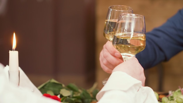 Senior couple raising toast during mealtime in a restaurant. relaxed couple. drinking wine.