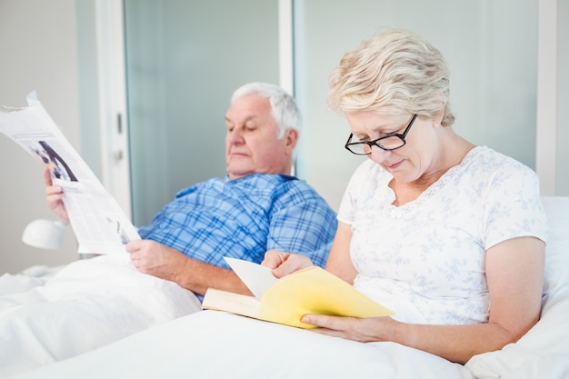 Senior couple reading on bed