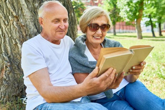 Senior couple reading a book outside