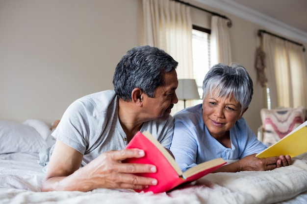 Senior couple reading books on bed