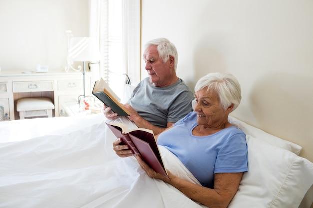 自宅の寝室で本を読んでいる年配のカップル