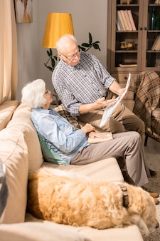 Пожилая пара читает газету дома