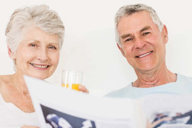 Senior couple reading newspaper at bed