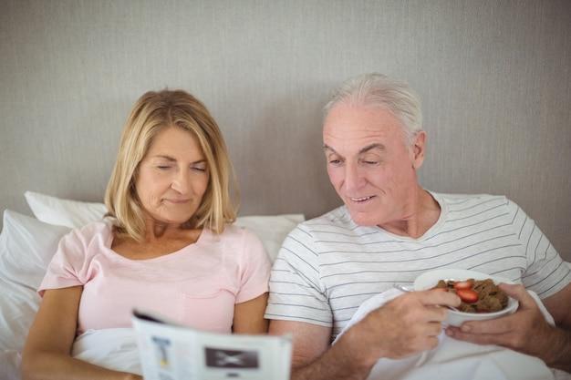 朝食をとりながら新聞を読んで年配のカップル