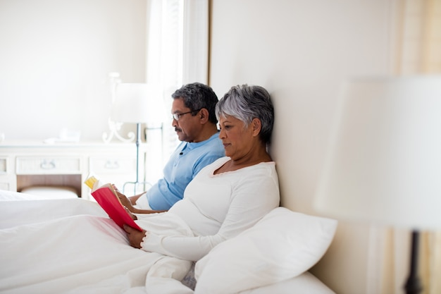Senior couple reading a novel in living room