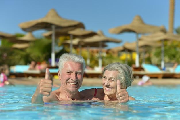 엄지손가락으로 호텔 리조트 수영장에서 휴식을 취하는 수석 커플